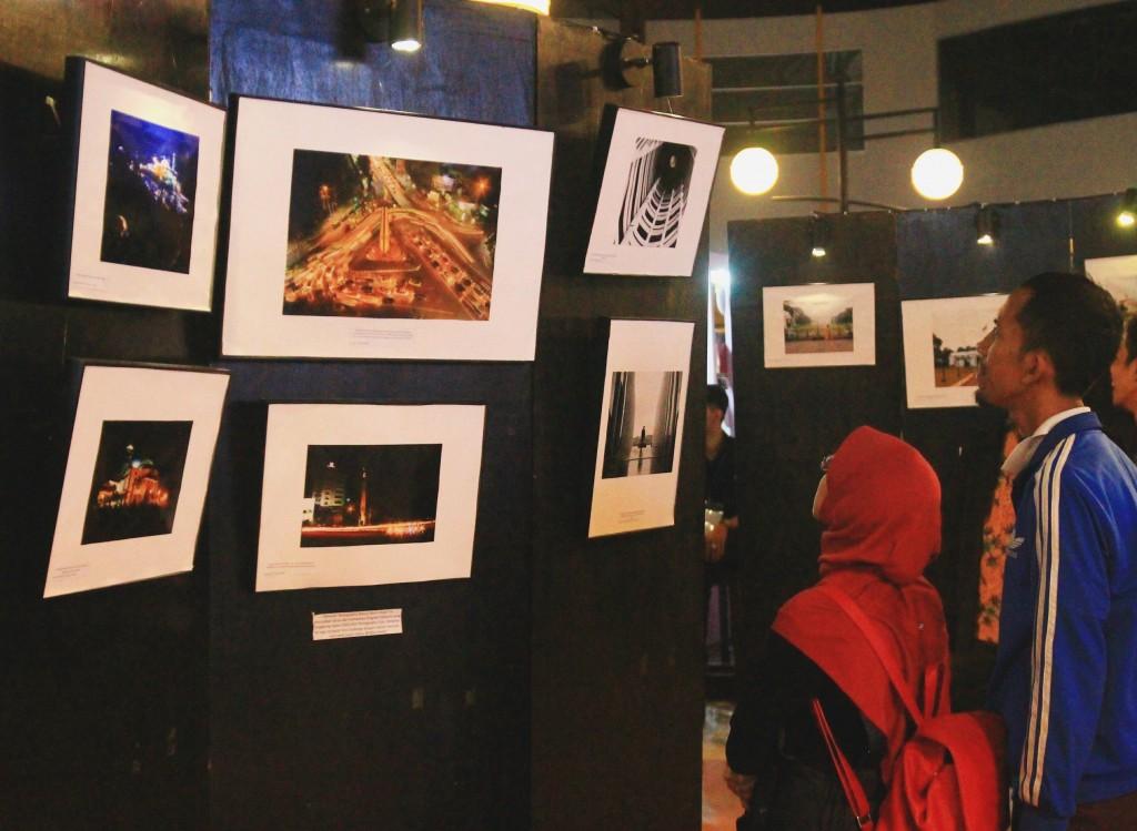 Pengunjung menikmati foto-foto yang disajikan pada pameran, Sabtu(7/11). (Foto: Nita F)