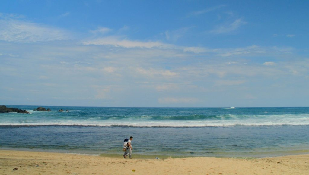 Dua sejoli yang sedang menyusuri pasir putih yang beratap lagit biru dengan desiran ombak Pantai Siung (5/5/2016). (foto oleh: Herlinda Y.)