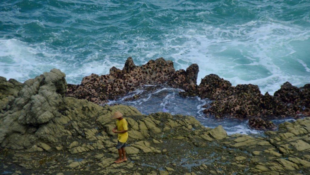 Seorang nelayan yang sedang berjalan di atas permukaan batu yang dikelilingi batu karang berukuran besar (5/5/2016). (foto oleh: Herlinda Y.)