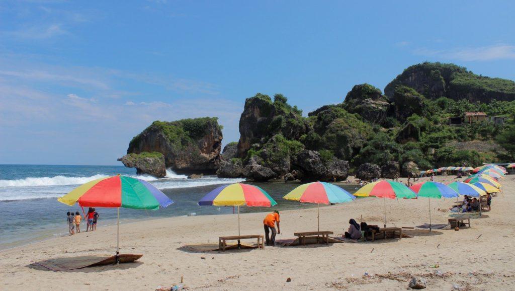 Payung warna-warni di sepanjang pantai dengan tikar menjulur di atas pasir putih yang disediakan untuk pengunjung bersantai sambil menikmati pemandangan Pantai Siung yang indah (5/5/2016). (foto oleh: Herlinda Y.)