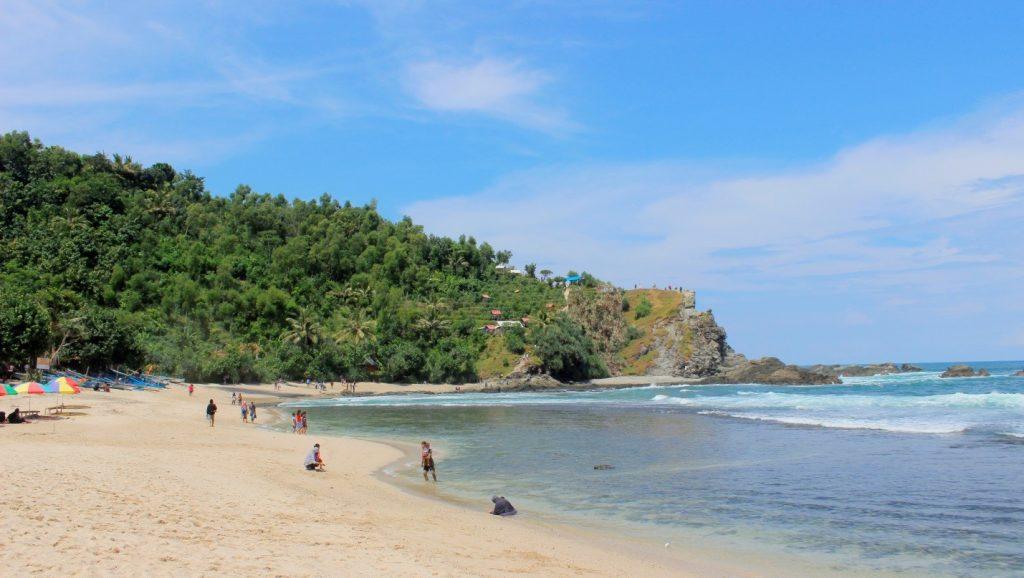 Hamparan pasir putih dan bukit di sisi Barat Pantai Siung yang bernaung di bawah langit biru. Di atas bukit ini kita dapat menikmati pemandangan keseluruhan pantai dan karang-karang besar di sisi kiri dan kanan (5/5/2016). (foto oleh: Herlinda Y.)